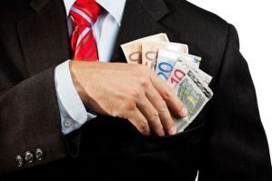 Businessman putting money in his pocket.